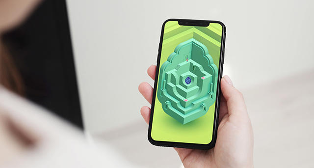 Hand holding mobile phone showcasing Monument Valley 2